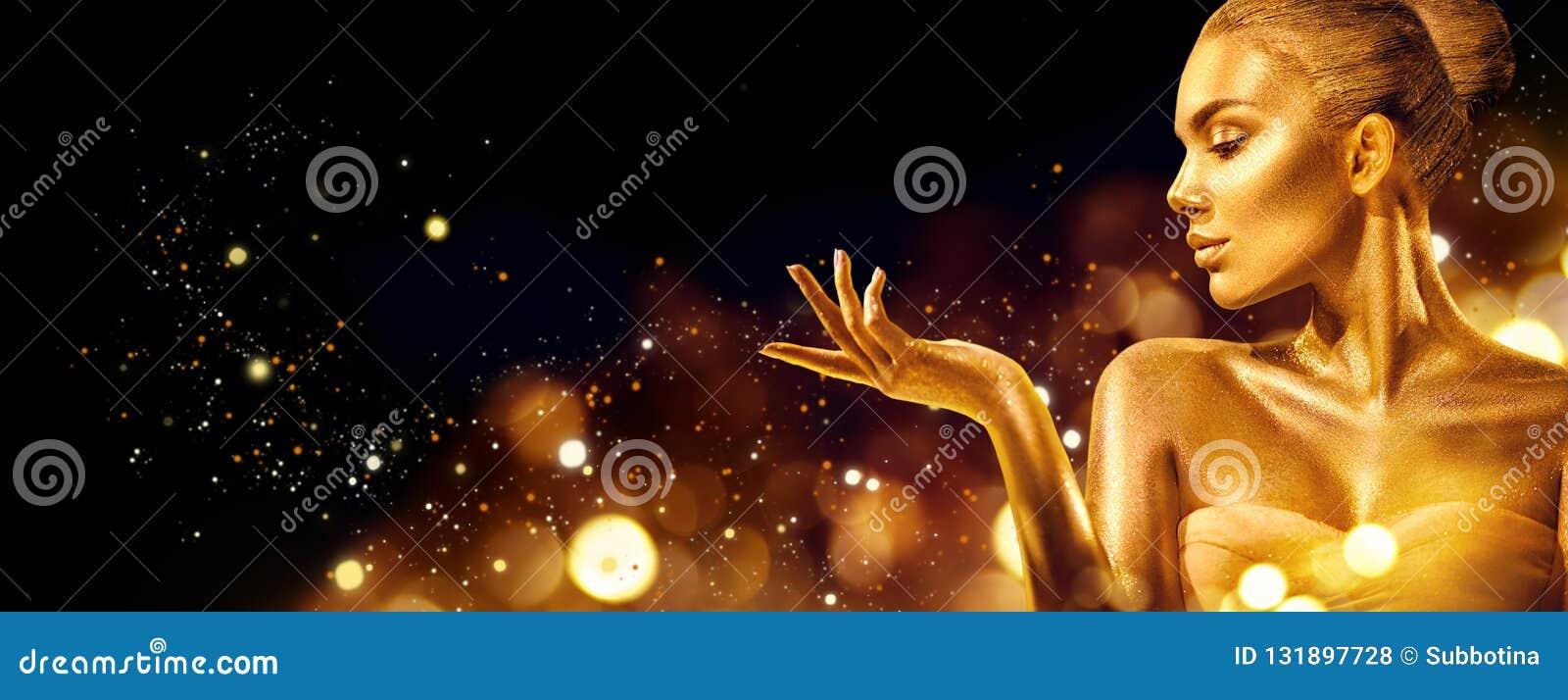 Mujer de la Navidad del oro Muchacha del modelo de moda de la belleza con maquillaje de oro, pelo y joyería señalando la mano en
