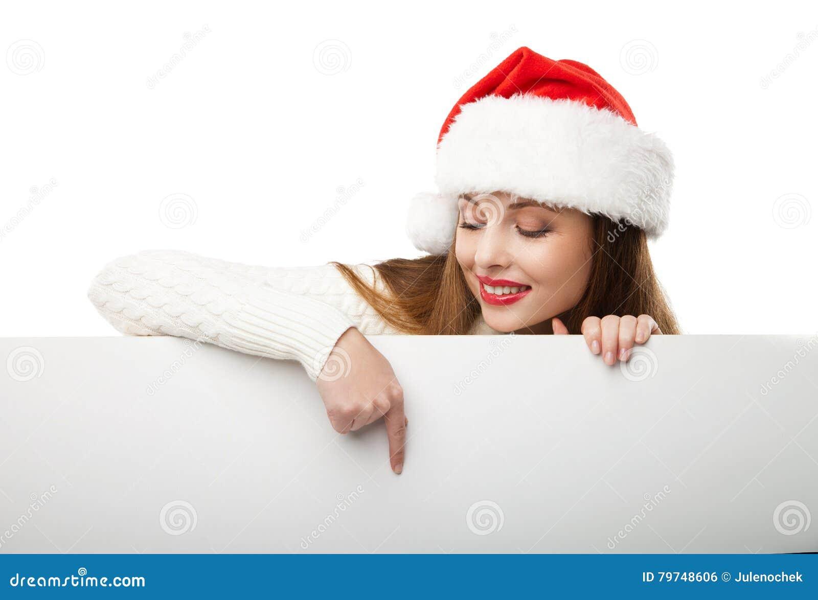 Mujer de la Navidad en el sombrero de santa que señala al tablero vacío