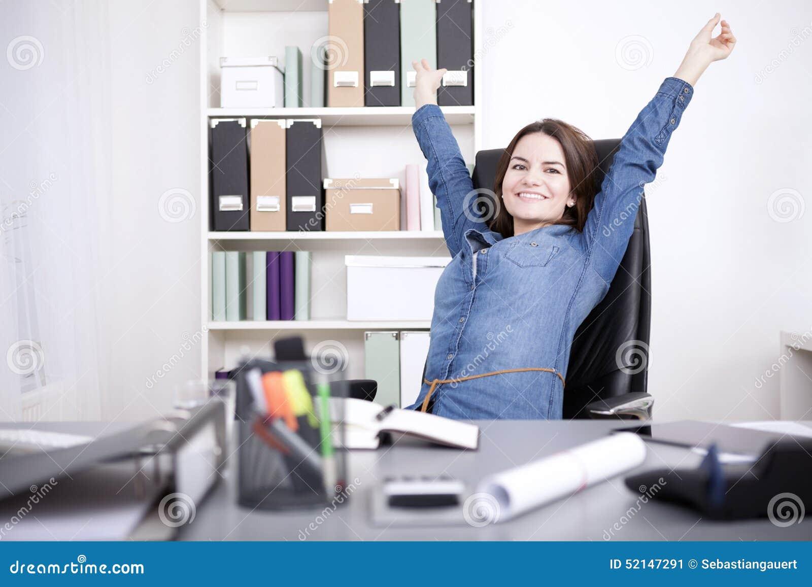 Mujer de la oficina que se sienta en la silla que estira sus brazos