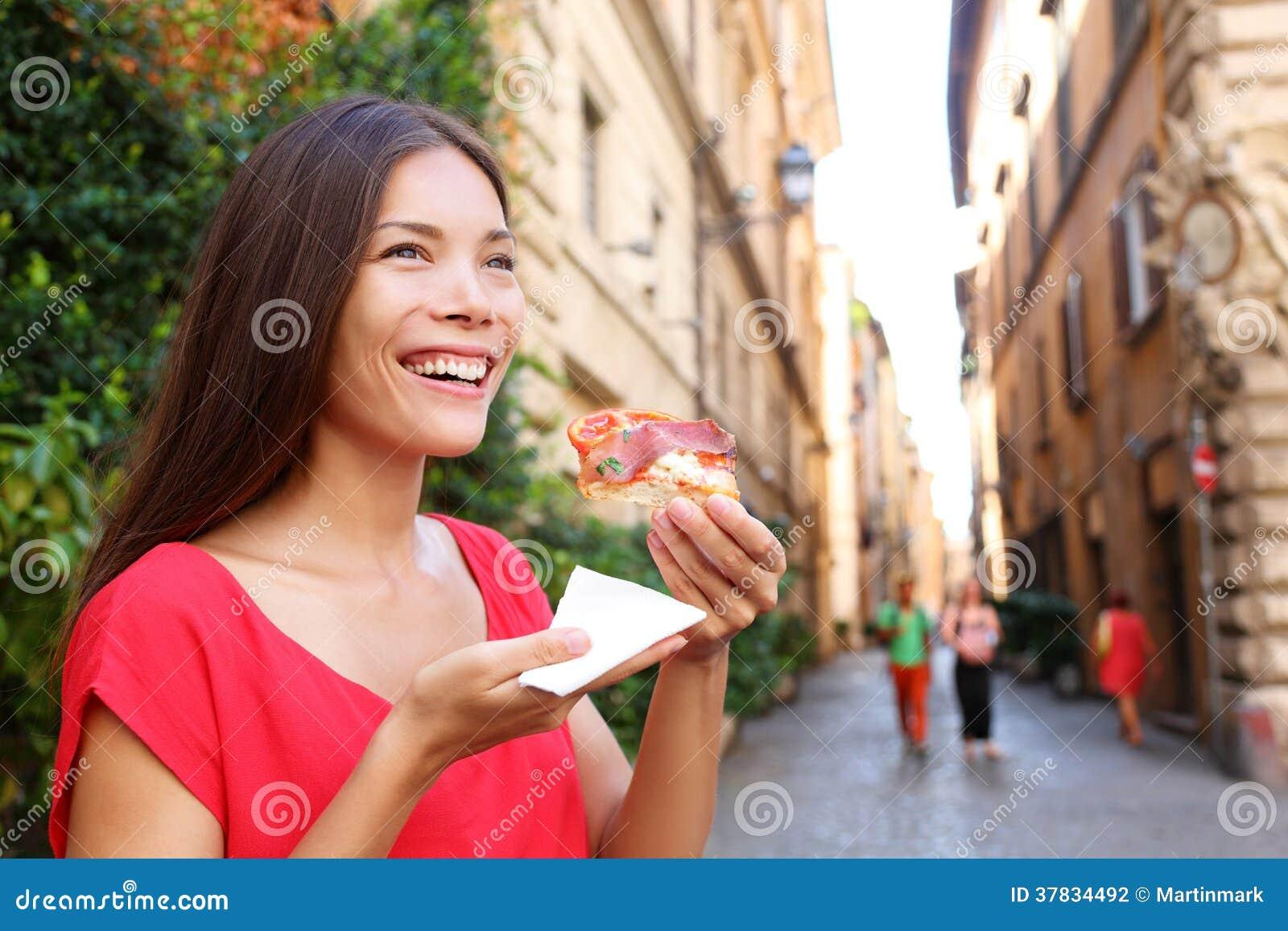 Mujer de la pizza que come la rebanada de la pizza en Roma, Italia