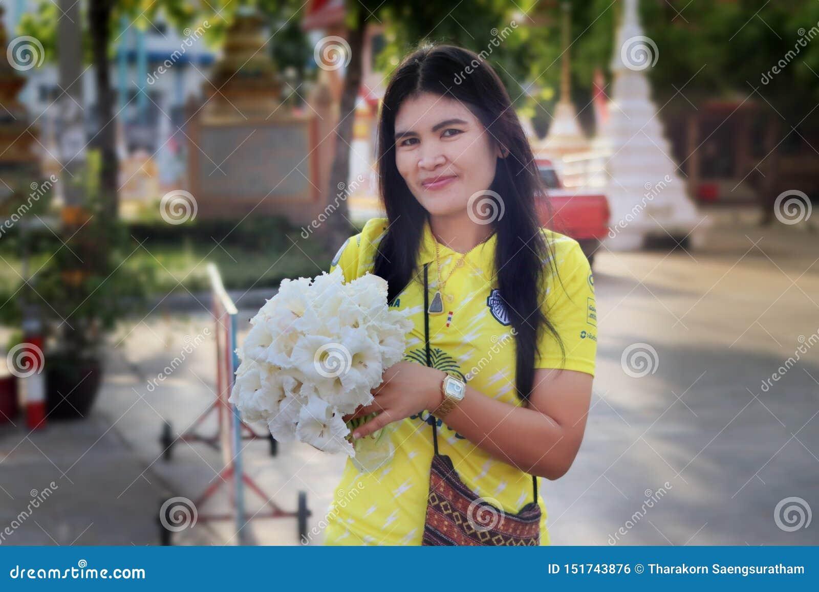 Mujer de la sonrisa mantener las flores comestibles para una comida comida la mañana en marzo 15,2016 en el parque público de Ban
