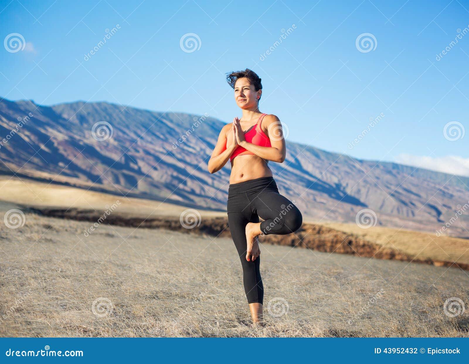 Mujer de la yoga que practica en una playa