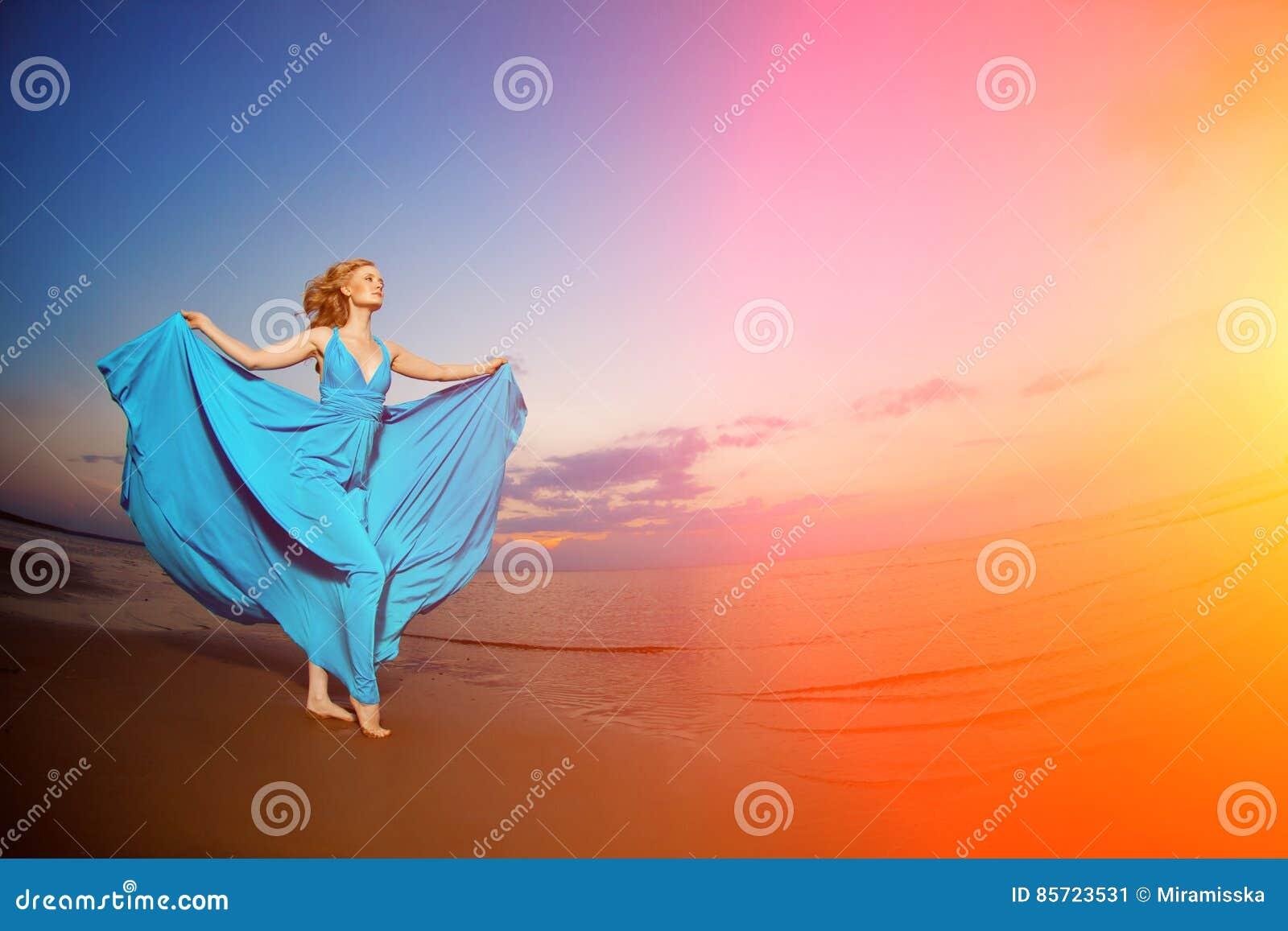 Mujer de lujo en un vestido de noche azul largo en la playa belleza