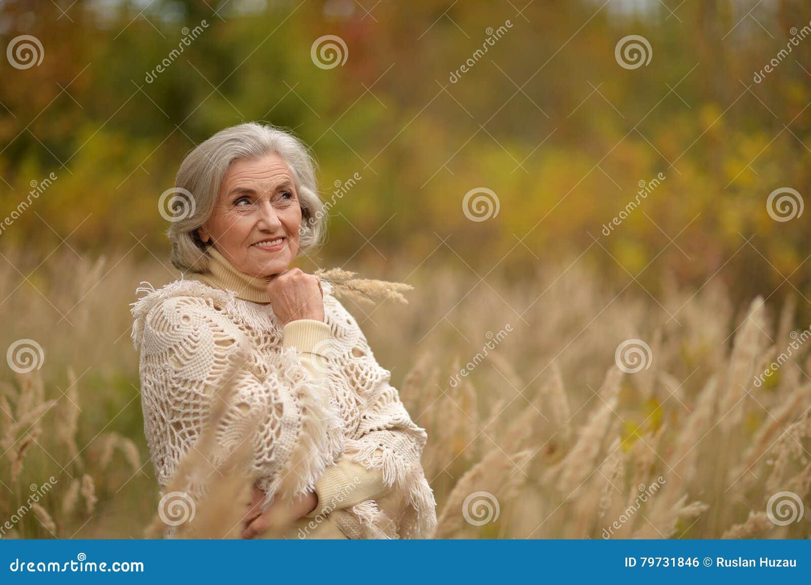 Mujer de mediana edad hermosa en parque del otoño