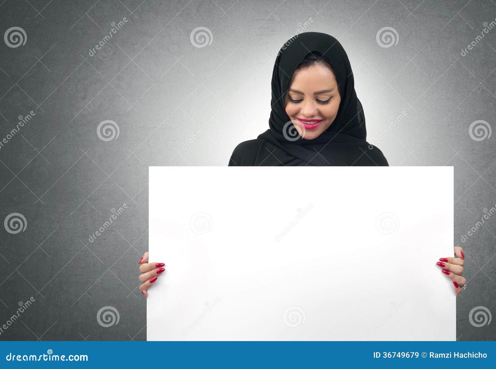 Mujer de negocios árabe que lleva a cabo a un tablero blanco aislado