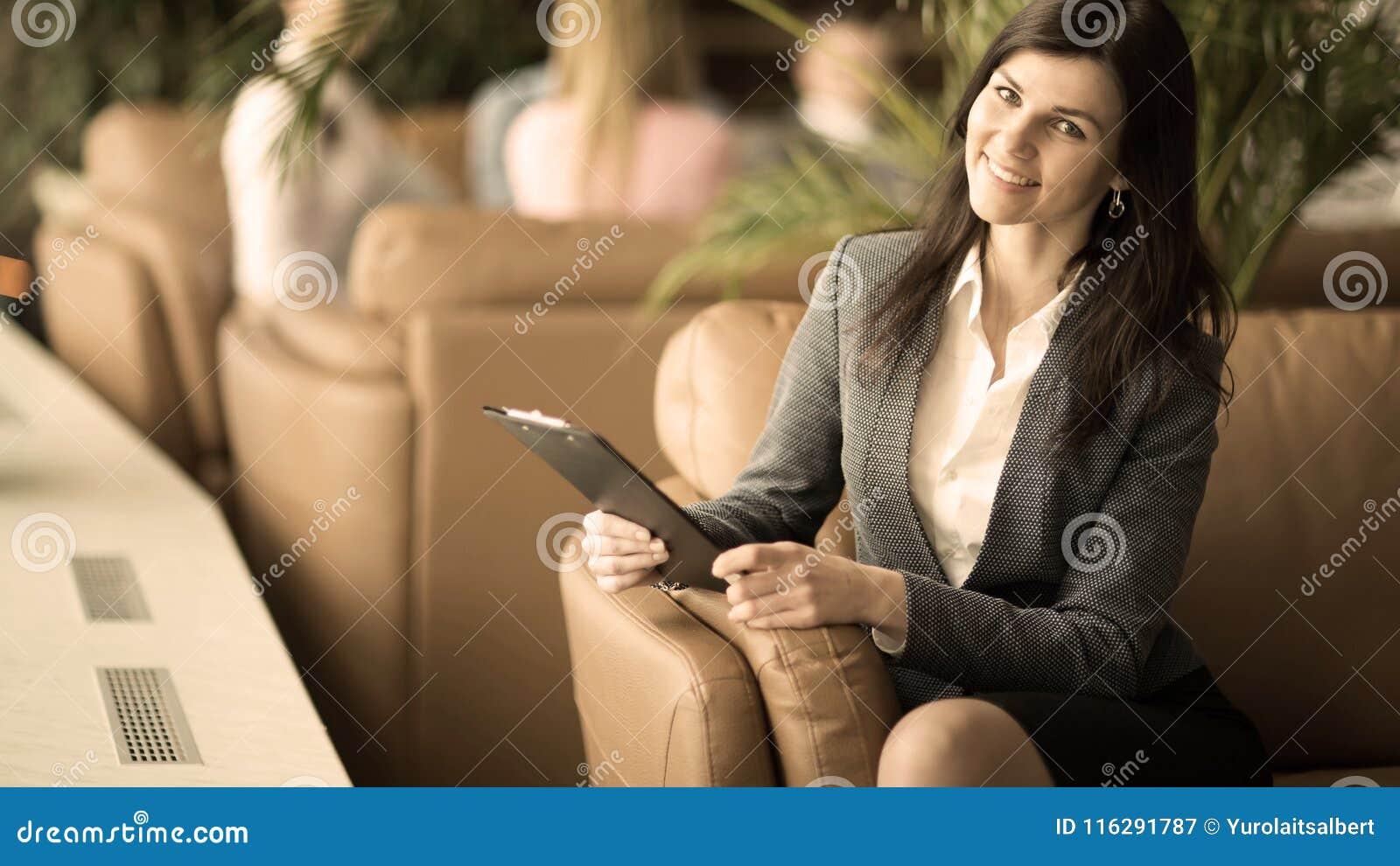 Mujer de negocios acertada con los documentos que se sientan en una silla en un pasillo de una oficina moderna