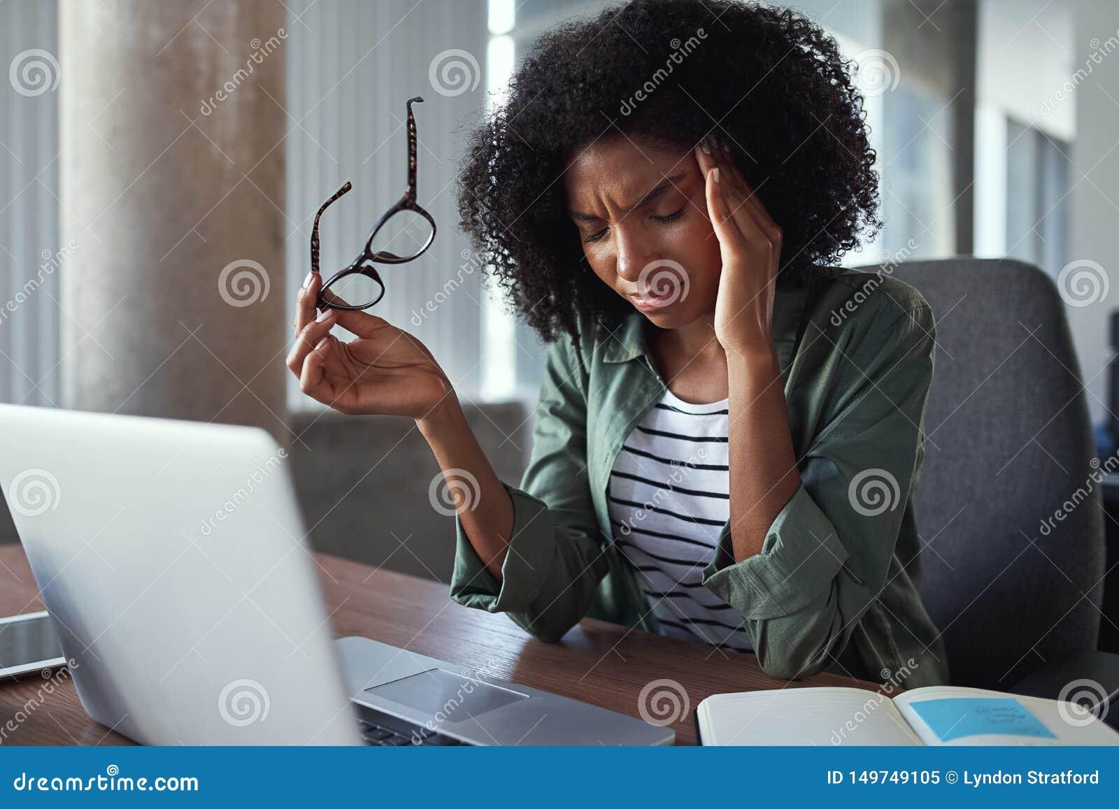 Mujer de negocios africana con exceso de trabajo con dolor de cabeza en la oficina