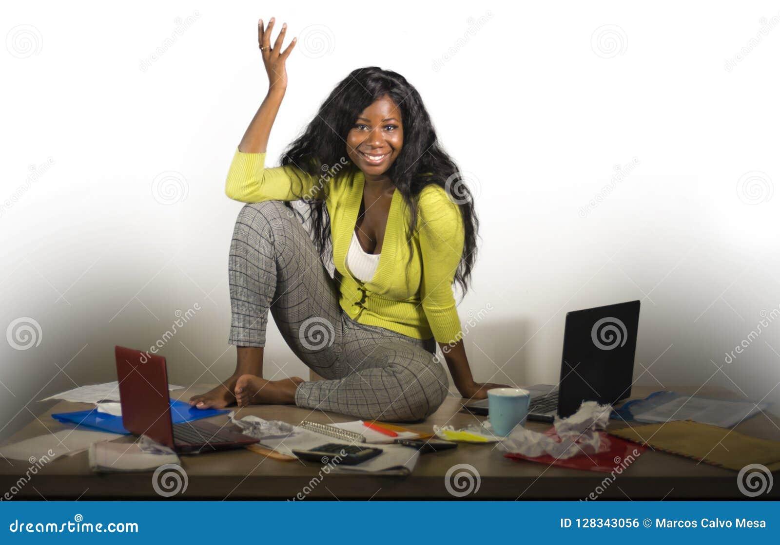 Mujer de negocios afroamericana feliz y atractiva joven que se sienta en el escritorio sucio de la oficina por completo de la son