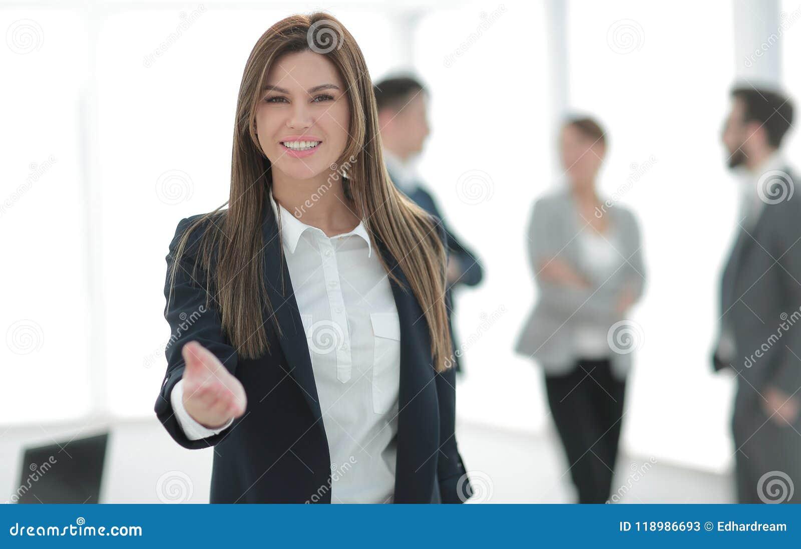 Mujer de negocios amistosa que lleva a cabo hacia fuera su mano para un apretón de manos
