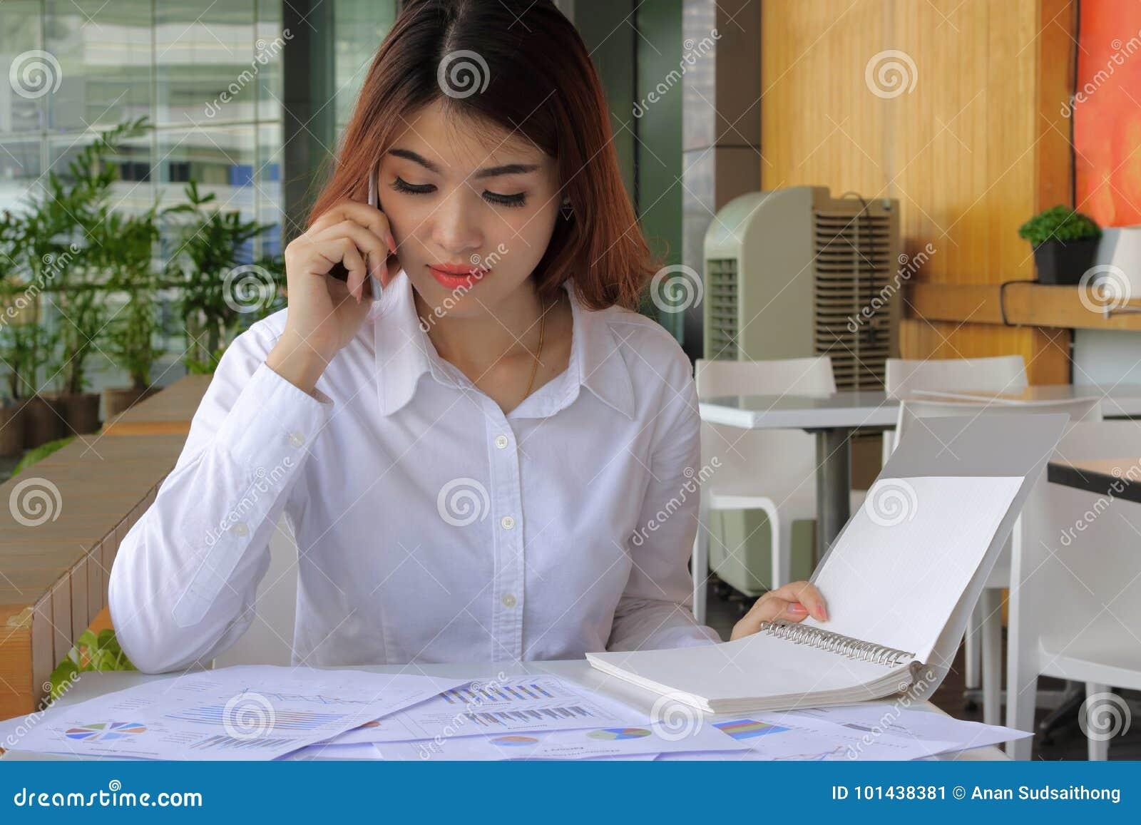 Mujer de negocios asiática atractiva joven que trabaja con el teléfono móvil, carta en oficina