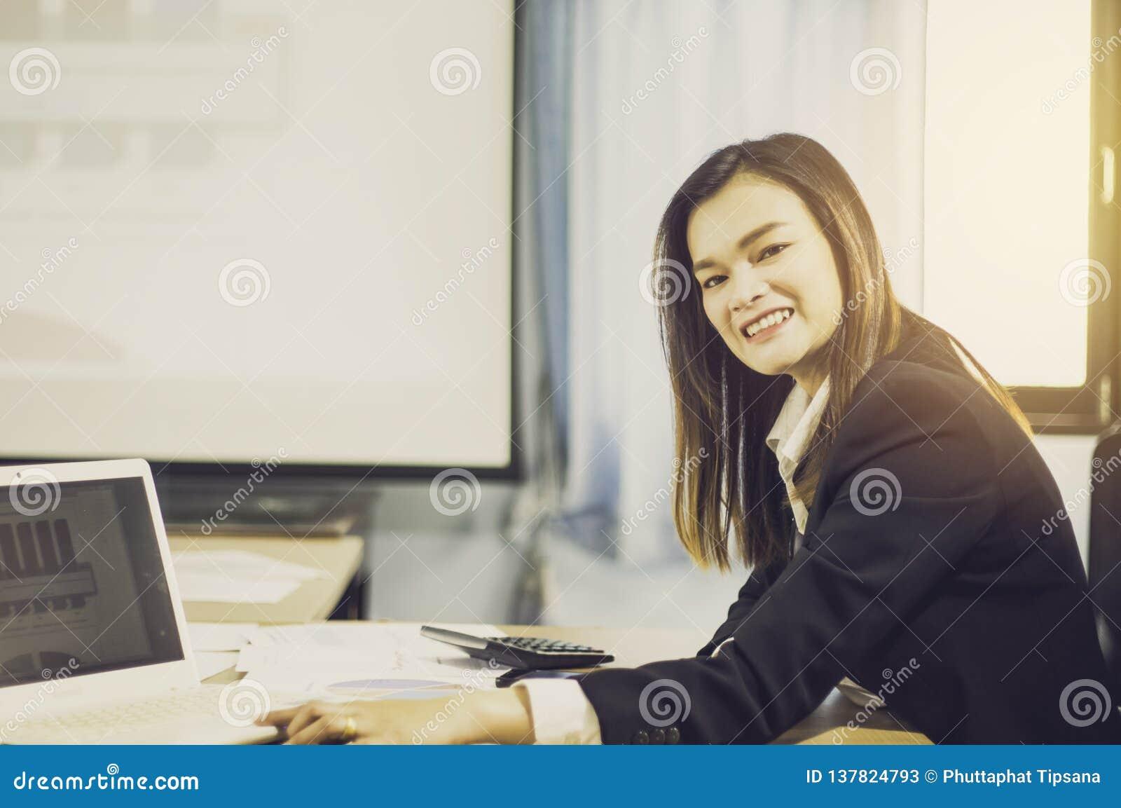 Mujer de negocios asiática del retrato con VR y teléfonos elegantes en la tabla, con las ventas de las auriculares de VR en el mu