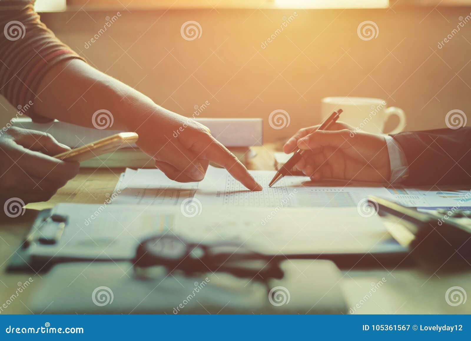 Mujer de negocios del trabajo en equipo que comprueba informe de las finanzas
