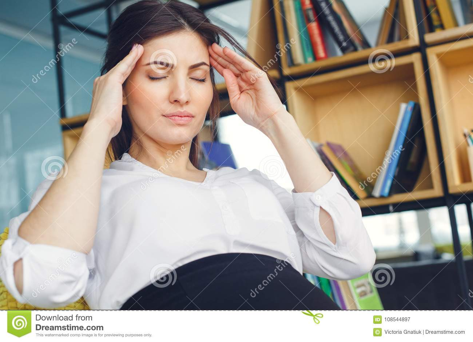 Mujer de negocios embarazada que trabaja en el dolor de cabeza que se sienta de la maternidad de la oficina