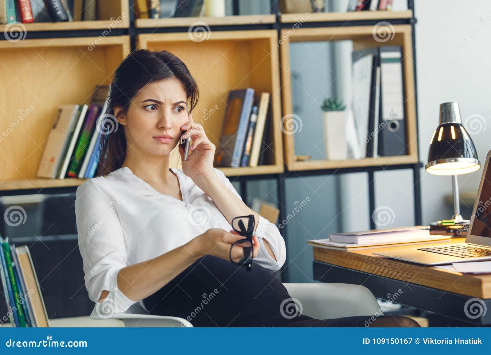 Mujer de negocios embarazada que trabaja en la conversación telefónica que se sienta de la maternidad de la oficina