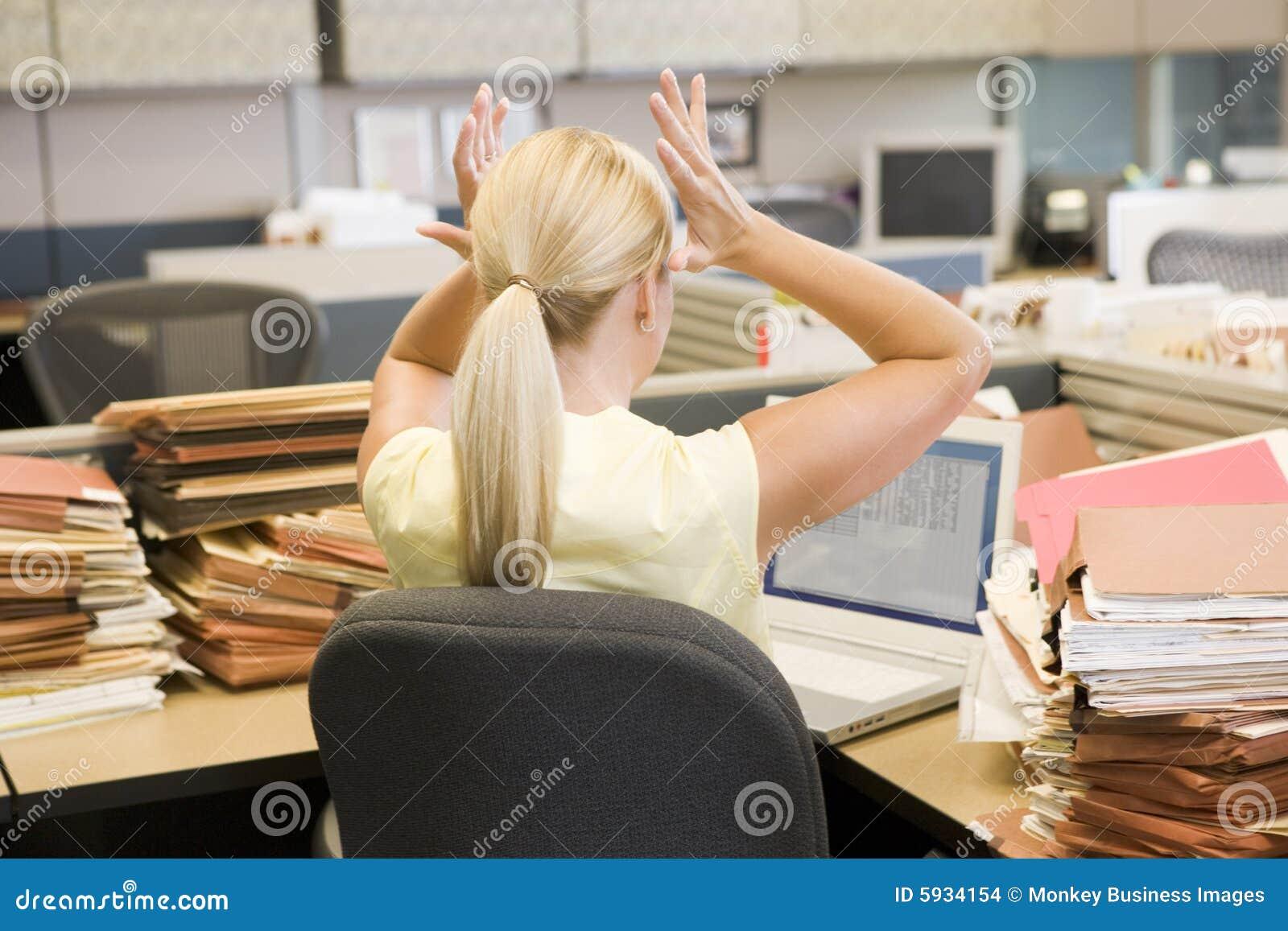 Mujer de negocios en el cubículo overworked y tensionado