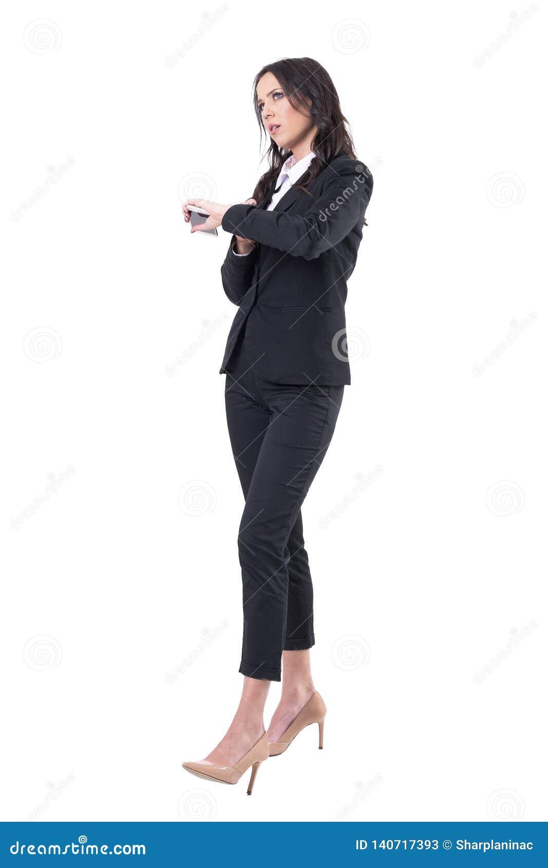 Mujer de negocios enfadada que comprueba el teléfono móvil de la tenencia del tiempo que espera alguien