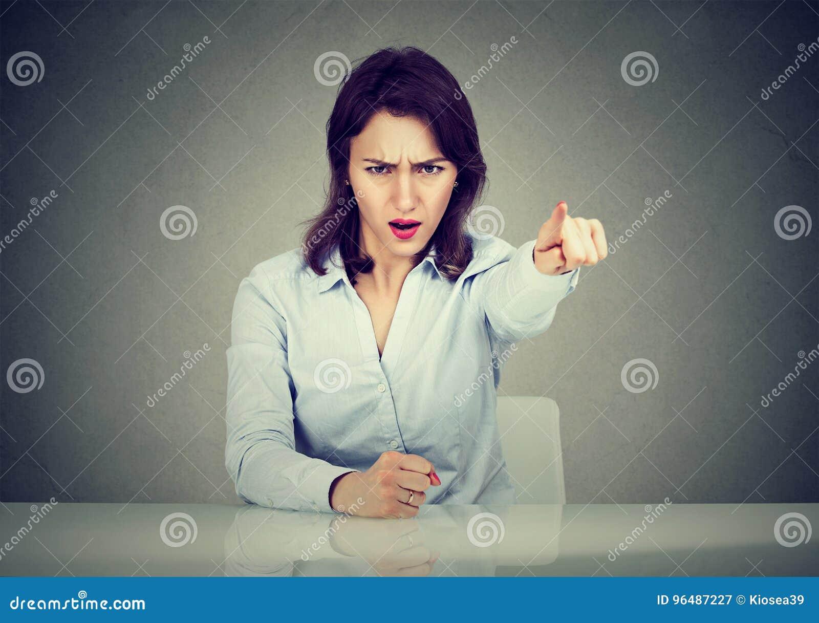 Mujer de negocios enojada que se sienta en señalar de griterío del escritorio con el finger a salir