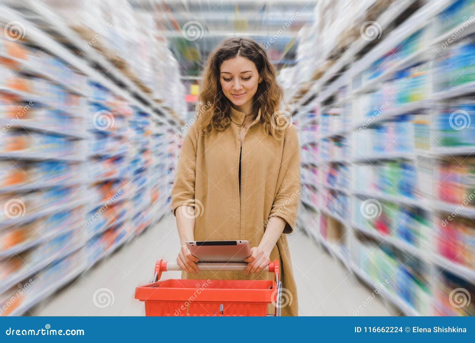 Mujer de negocios joven con un carro de compras que mira en una tableta en un supermercado entre los estantes