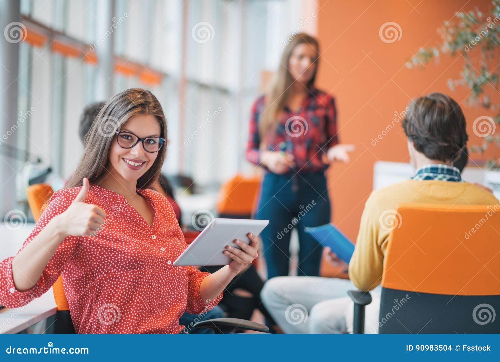 Mujer de negocios joven feliz con su personal, grupo de la gente en fondo en la oficina brillante moderna dentro