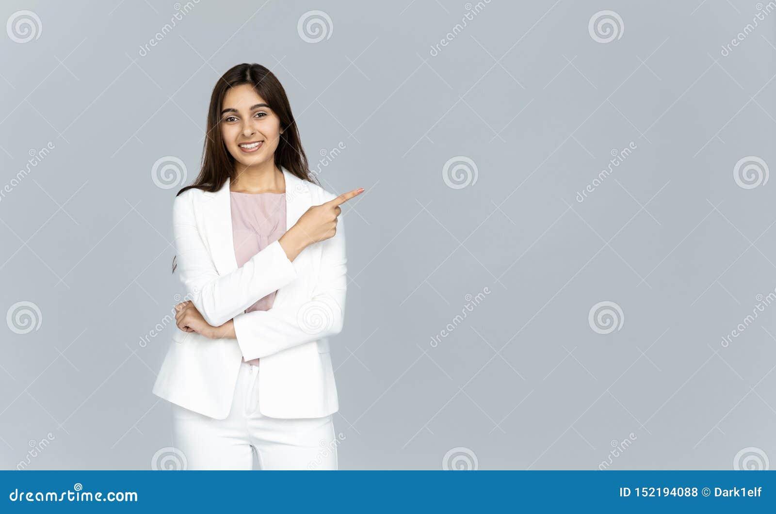 Mujer de negocios joven india feliz que mira la cámara que señala el finger en el copyspace