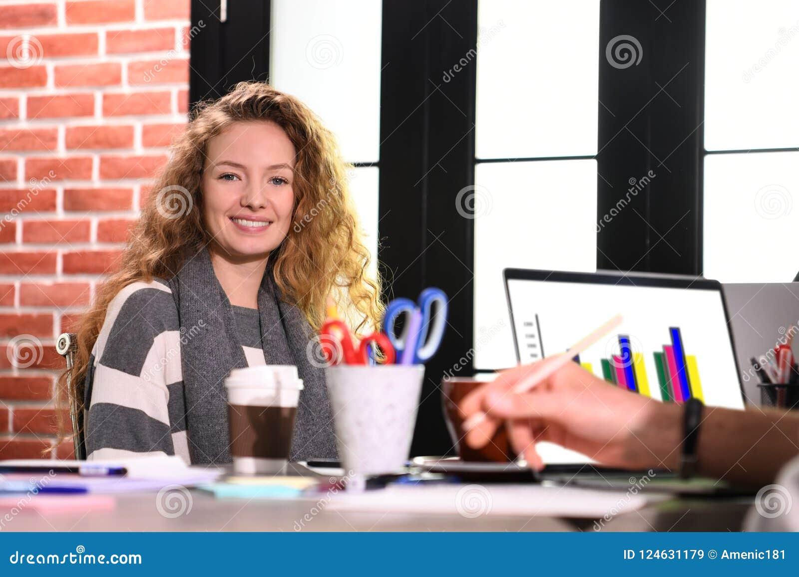 Mujer de negocios joven que se sienta en el escritorio en oficina