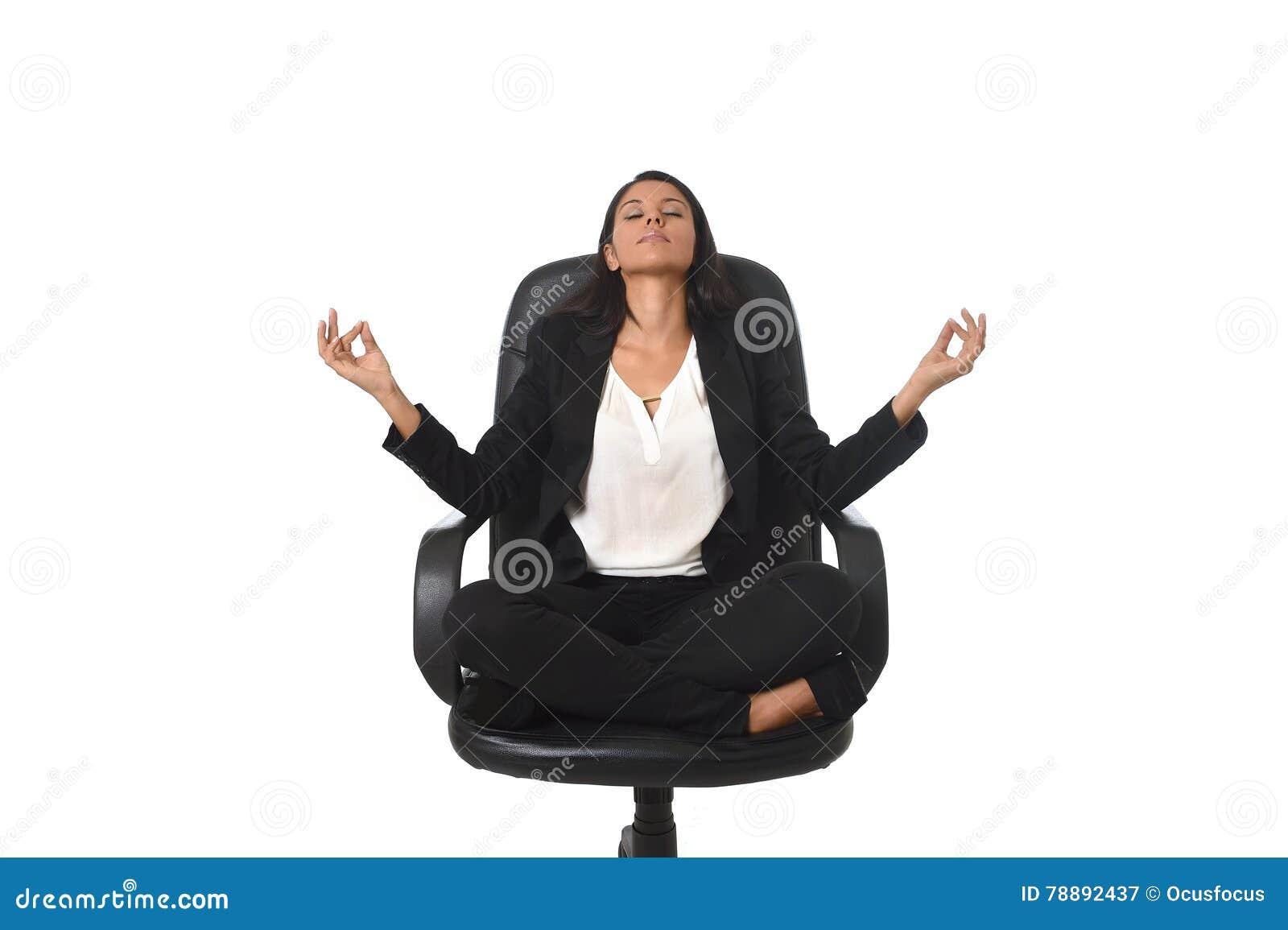 Mujer de negocios latinoamericana hermosa joven que se sienta en la silla de la oficina en yoga practicante de la postura del lot