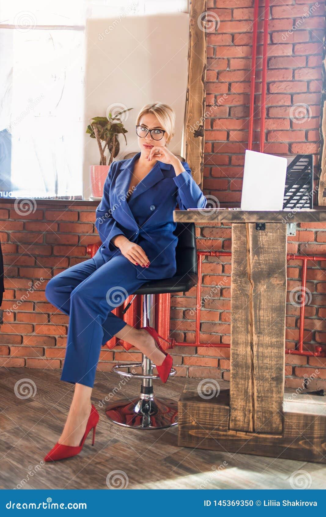 Mujer de negocios lista hermosa que se sienta en la tabla en el puesto de trabajo con el ordenador portátil