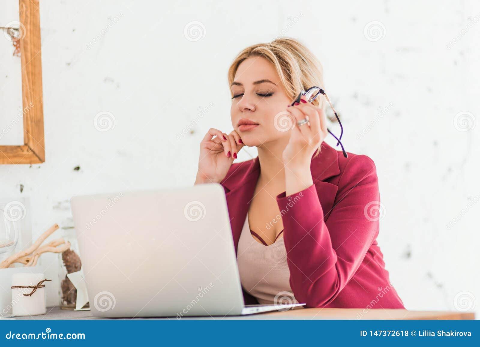Mujer de negocios lista hermosa que se sienta en la tabla en el puesto de trabajo con el ordenador port?til