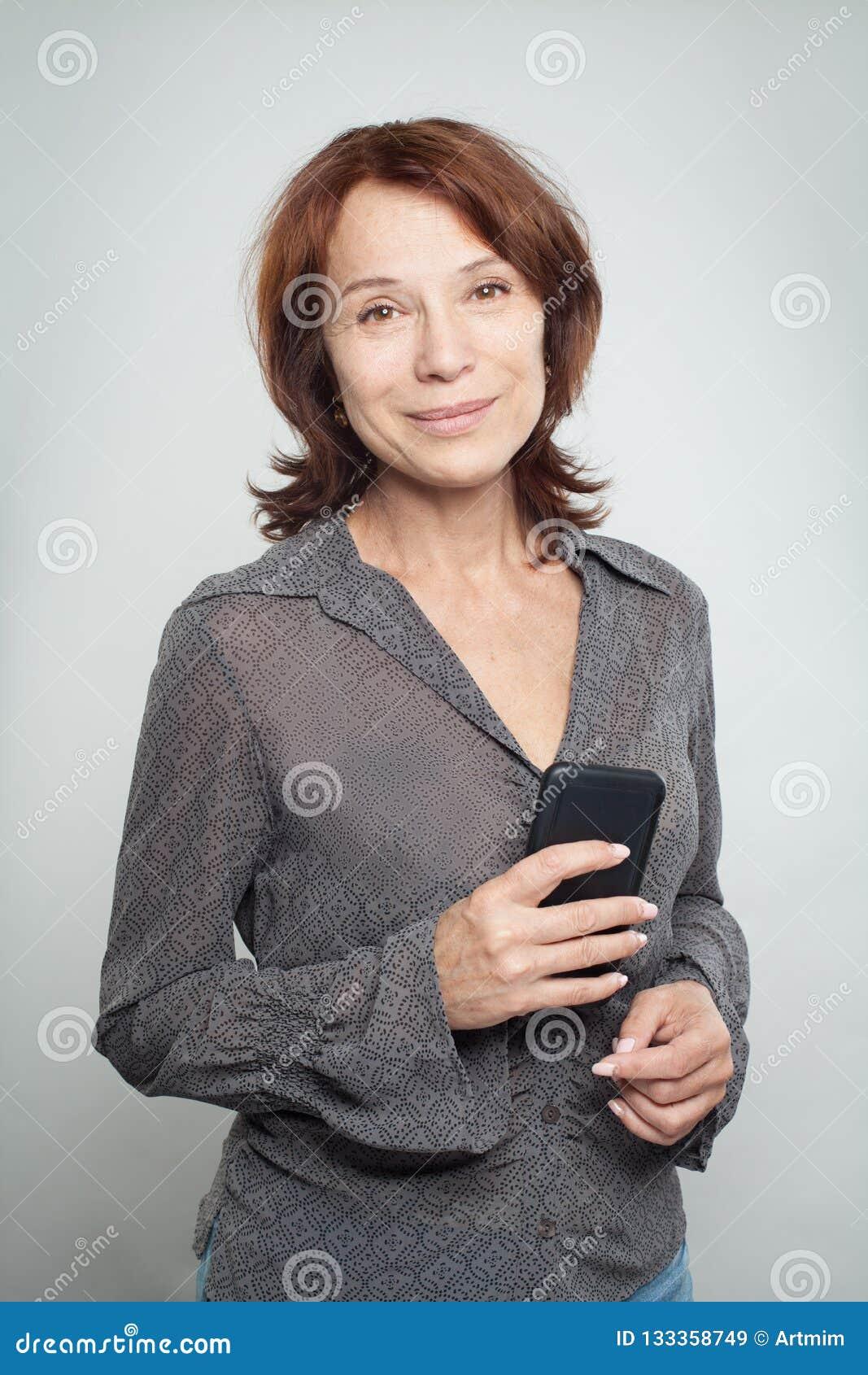 Mujer de negocios maduros feliz con el teléfono celular