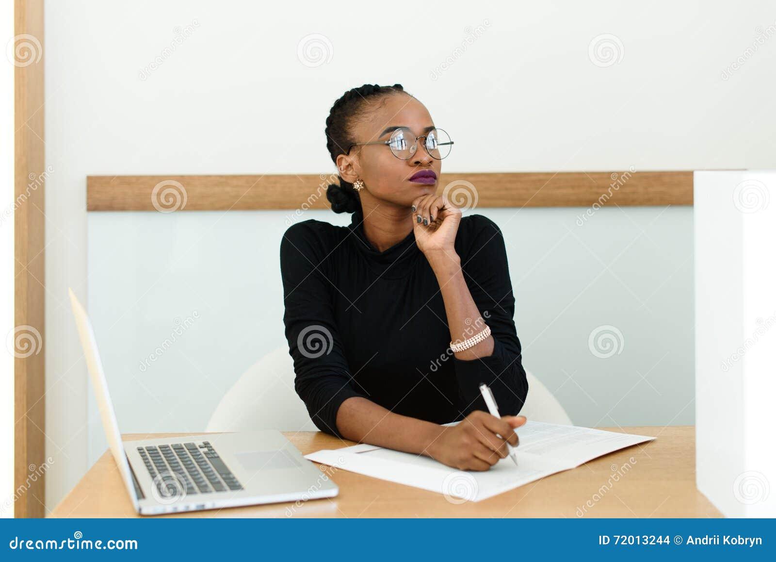 Mujer de negocios negra confiada en los vidrios que sostienen la barbilla que mira lejos el escritorio con la libreta y el ordena