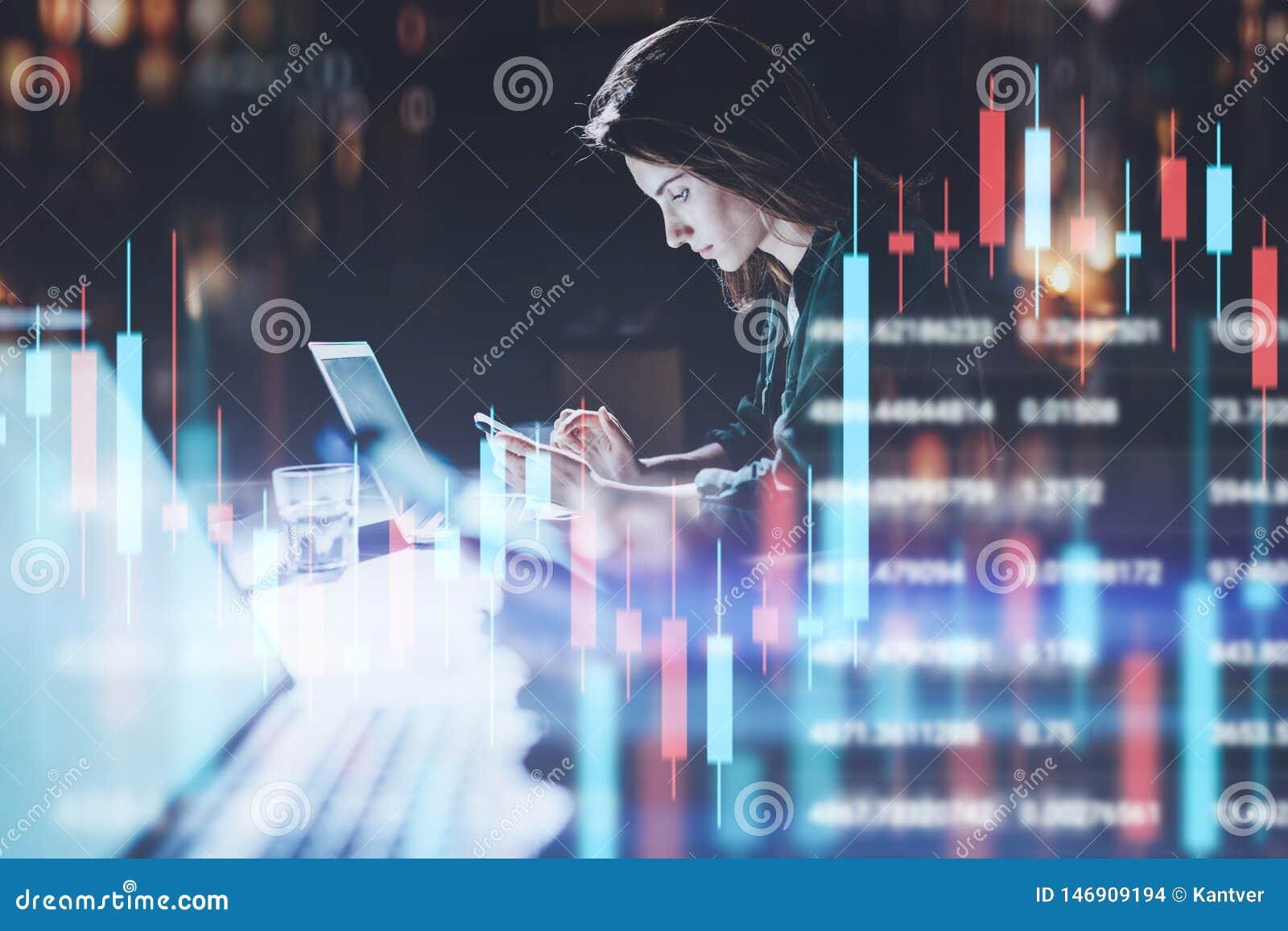 Mujer de negocios que se sienta en la oficina de la noche en ordenador portátil delantero con los gráficos financieros y que usa