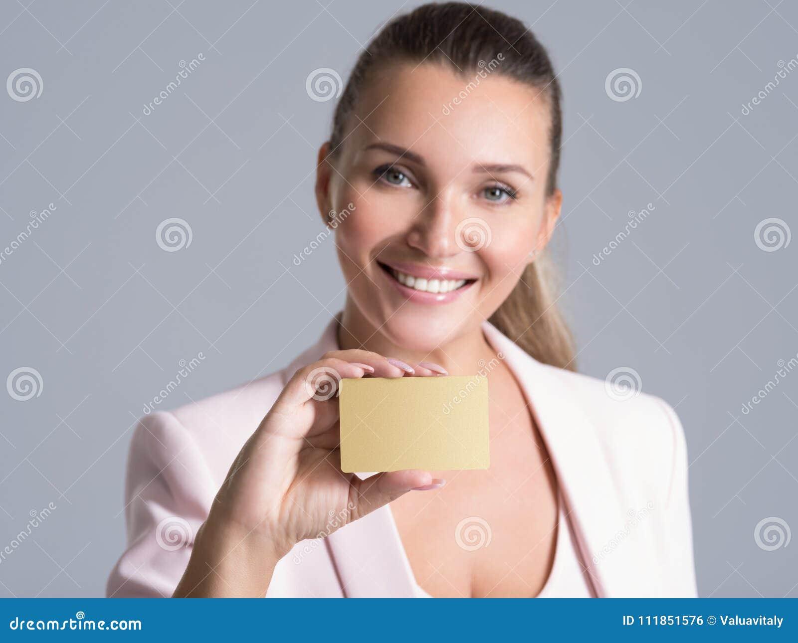 Mujer de negocios que sostiene la tarjeta de crédito contra su cara aislada