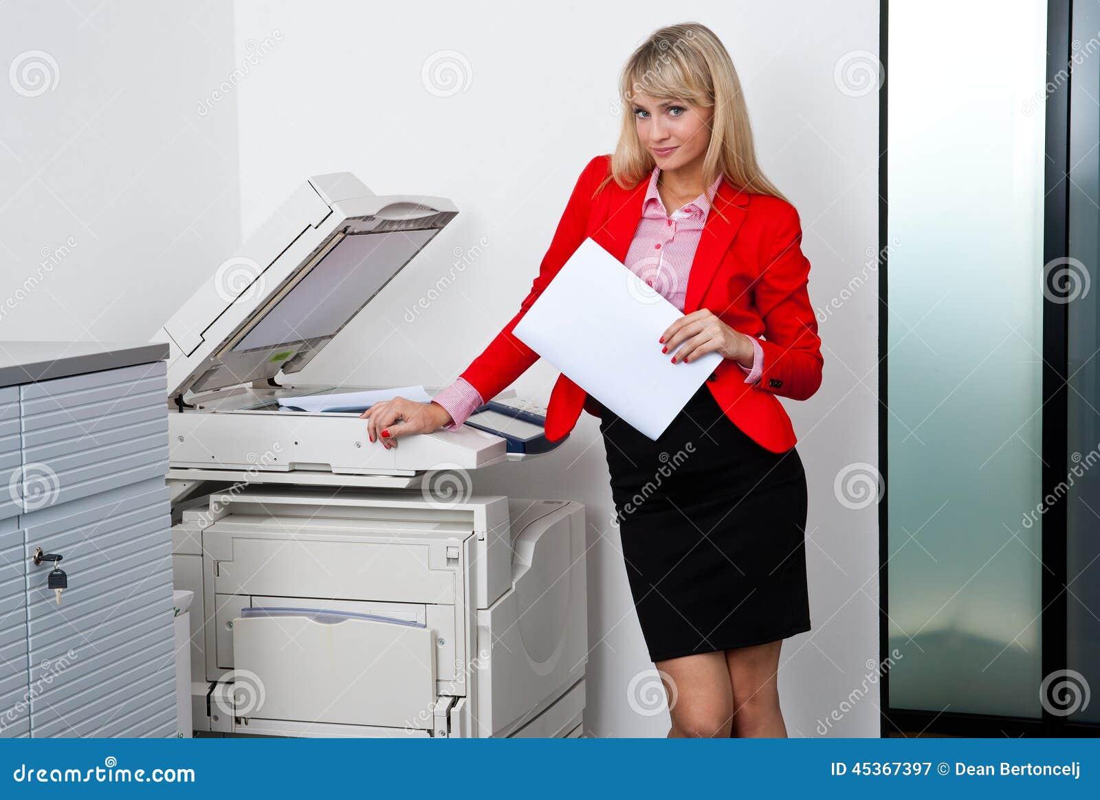 Mujer de negocios que trabaja en la impresora de oficina