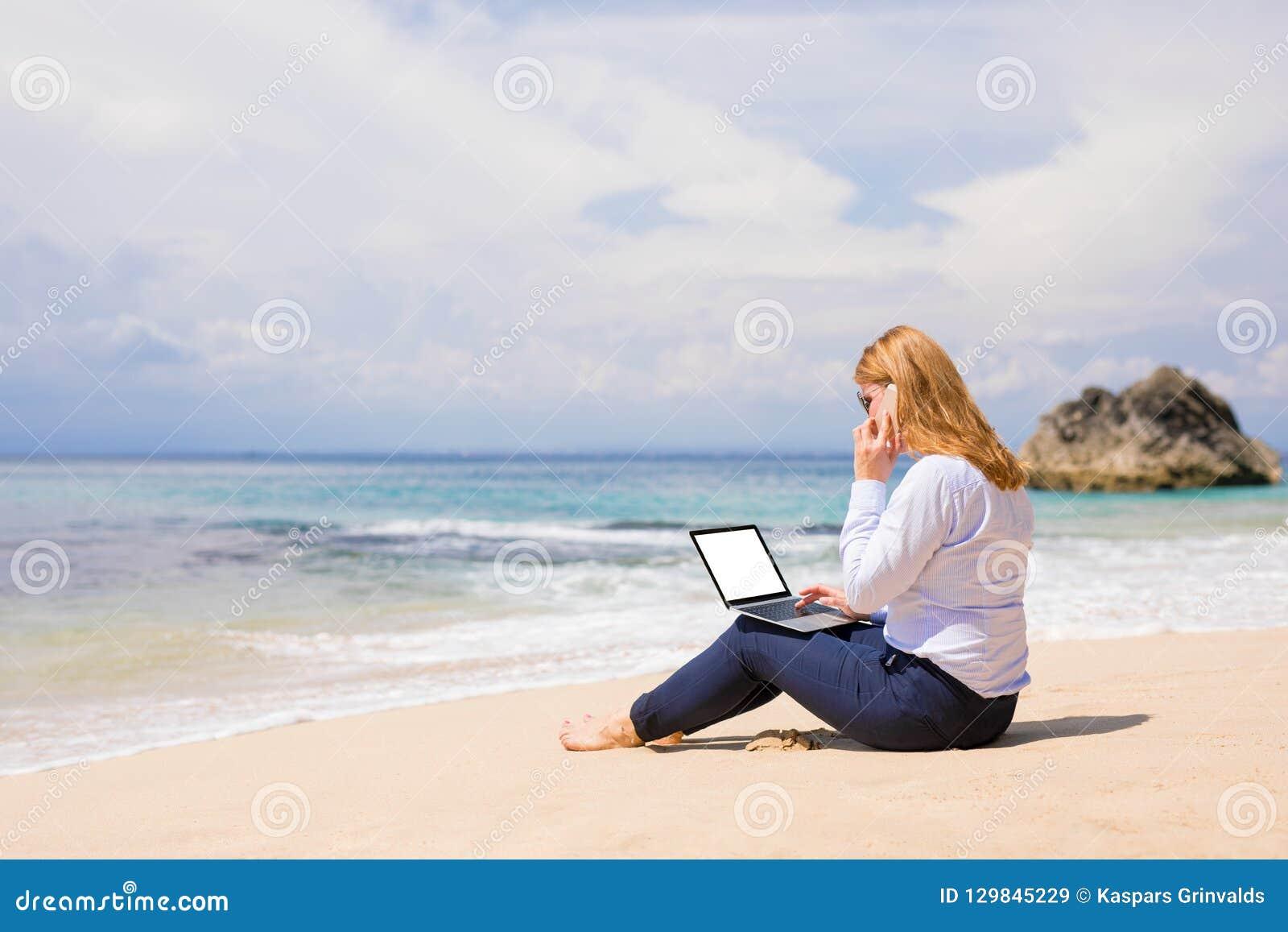 Mujer de negocios que trabaja en la playa