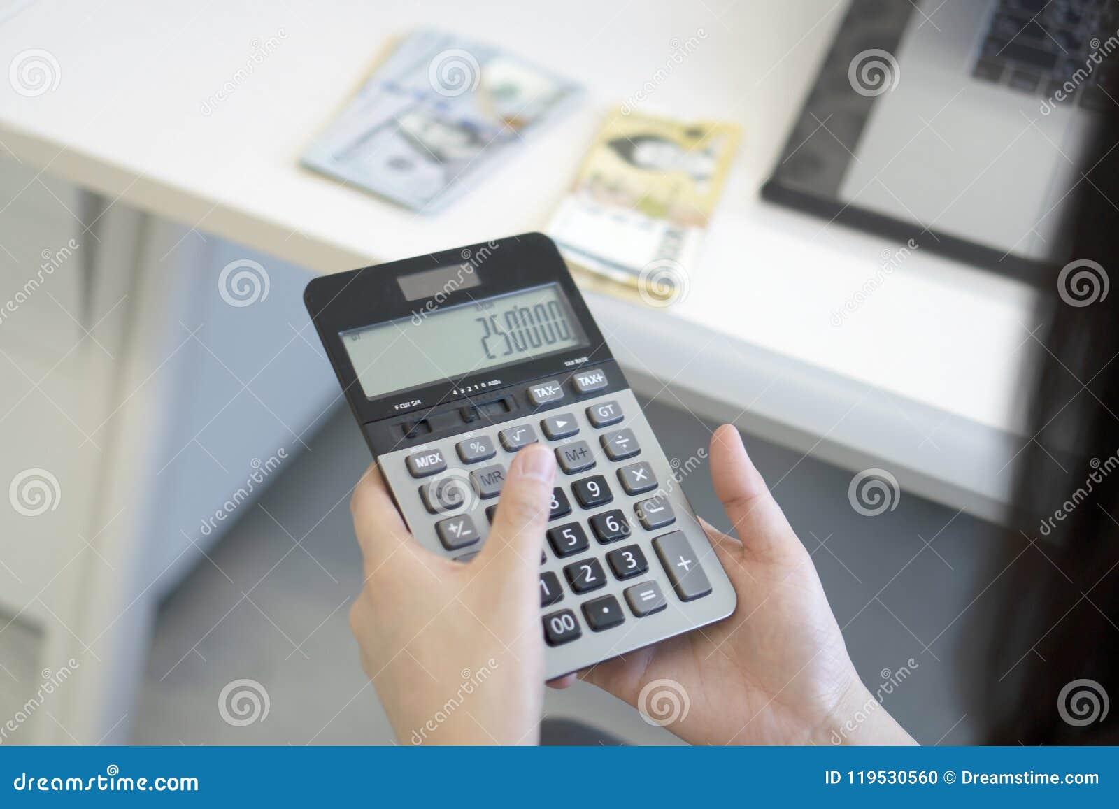 Mujer de negocios que usa la calculadora en oficina