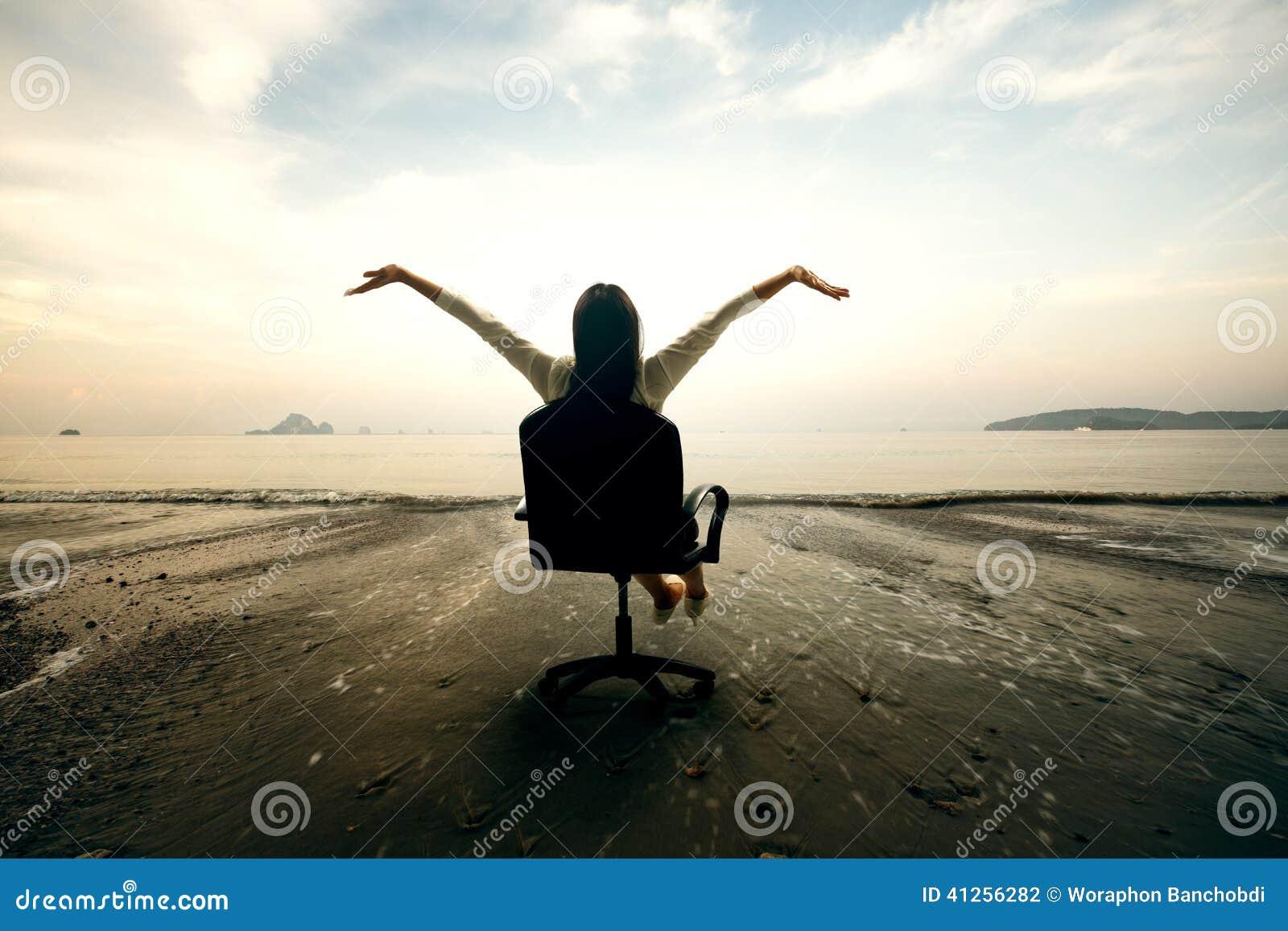Mujer de negocios relajante que se sienta en la playa