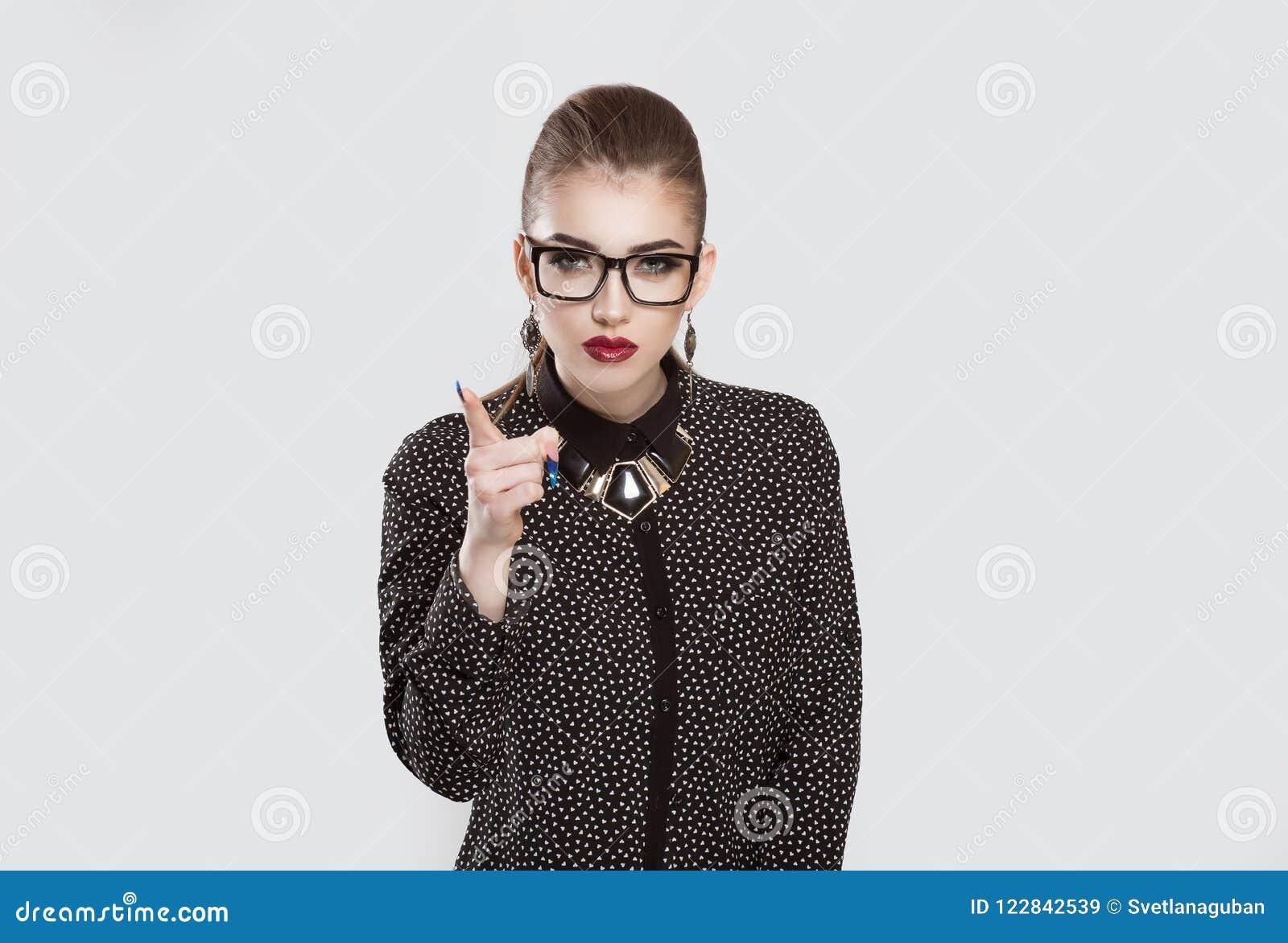 Mujer de negocios seria de la chica joven que muestra el dedo índice para la advertencia