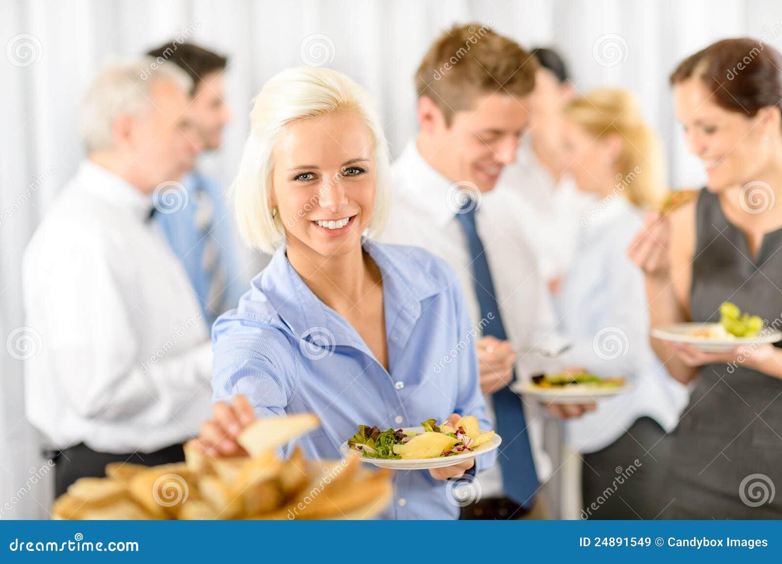 Mujer de negocios sonriente durante comida fría del almuerzo de la compañía