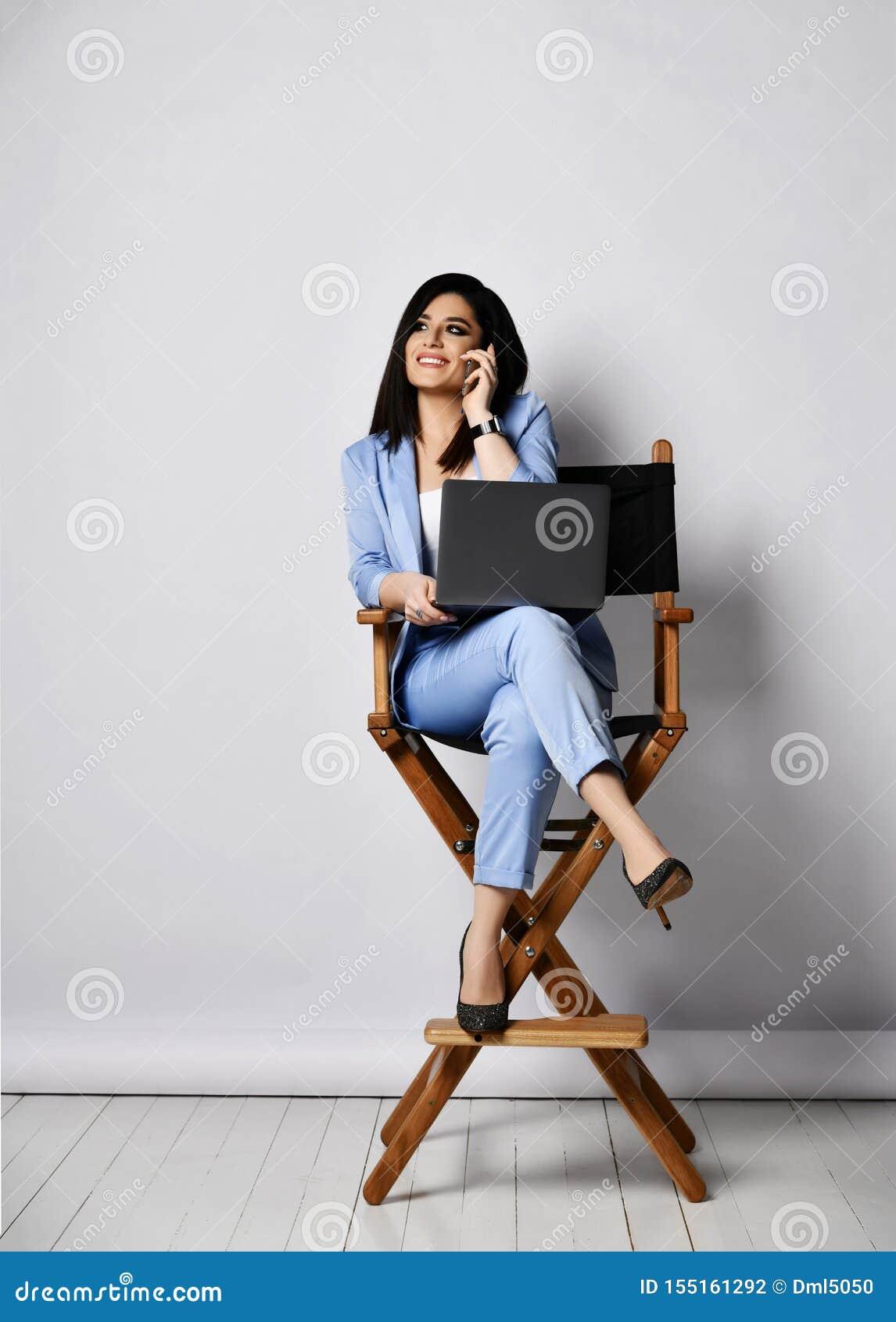 Mujer de negocios sonriente en traje oficial y los zapatos de tacón alto que se sientan con el ordenador portátil en la butaca y