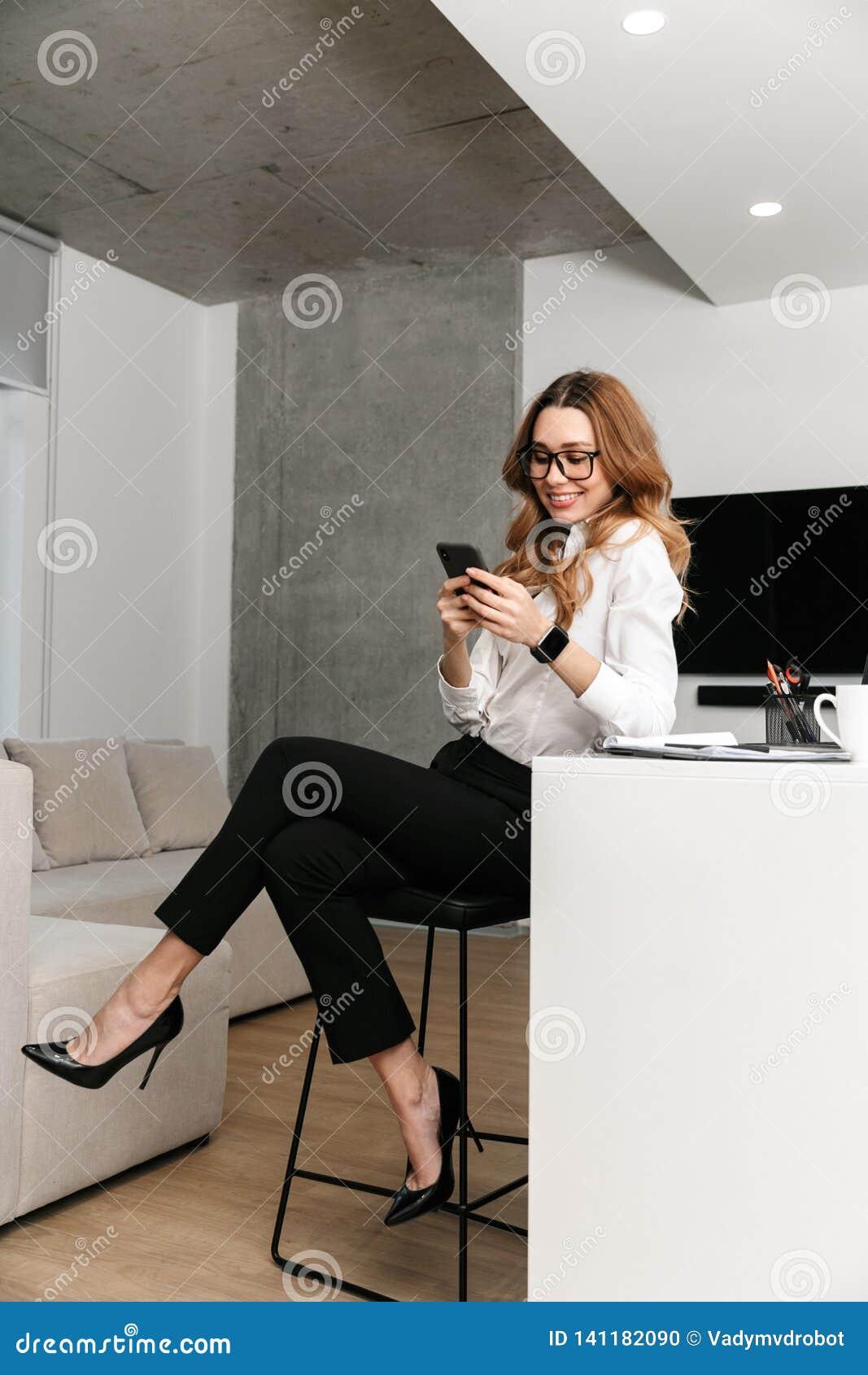 Mujer de negocios vestida en camisa formal de la ropa dentro usando el teléfono móvil