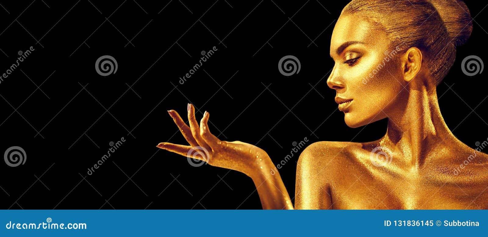 Mujer de oro Muchacha del modelo de moda de la belleza con la piel de oro, el maquillaje, el pelo y la joyería en fondo negro