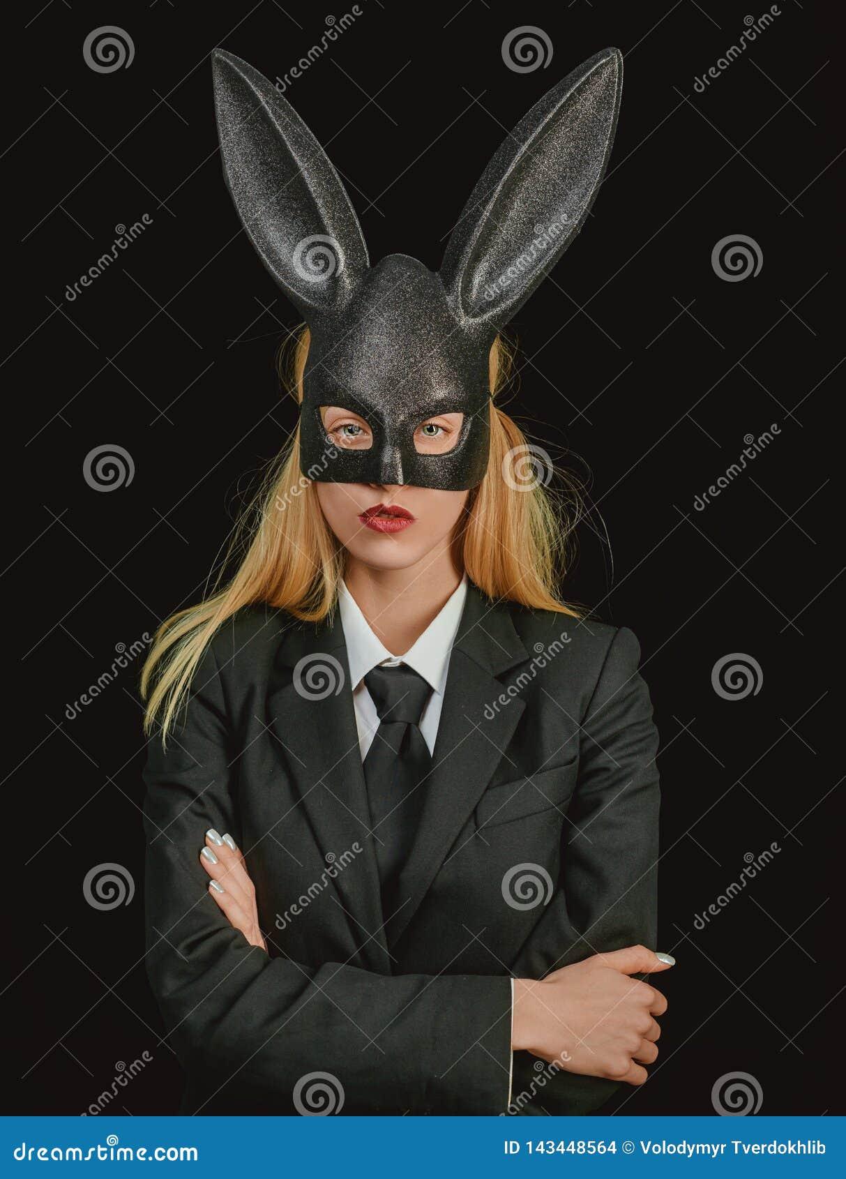 Mujer de Pascua Mujer atractiva con el conejito de pascua de la máscara en un fondo negro y miradas muy sensual Mujer feliz en co