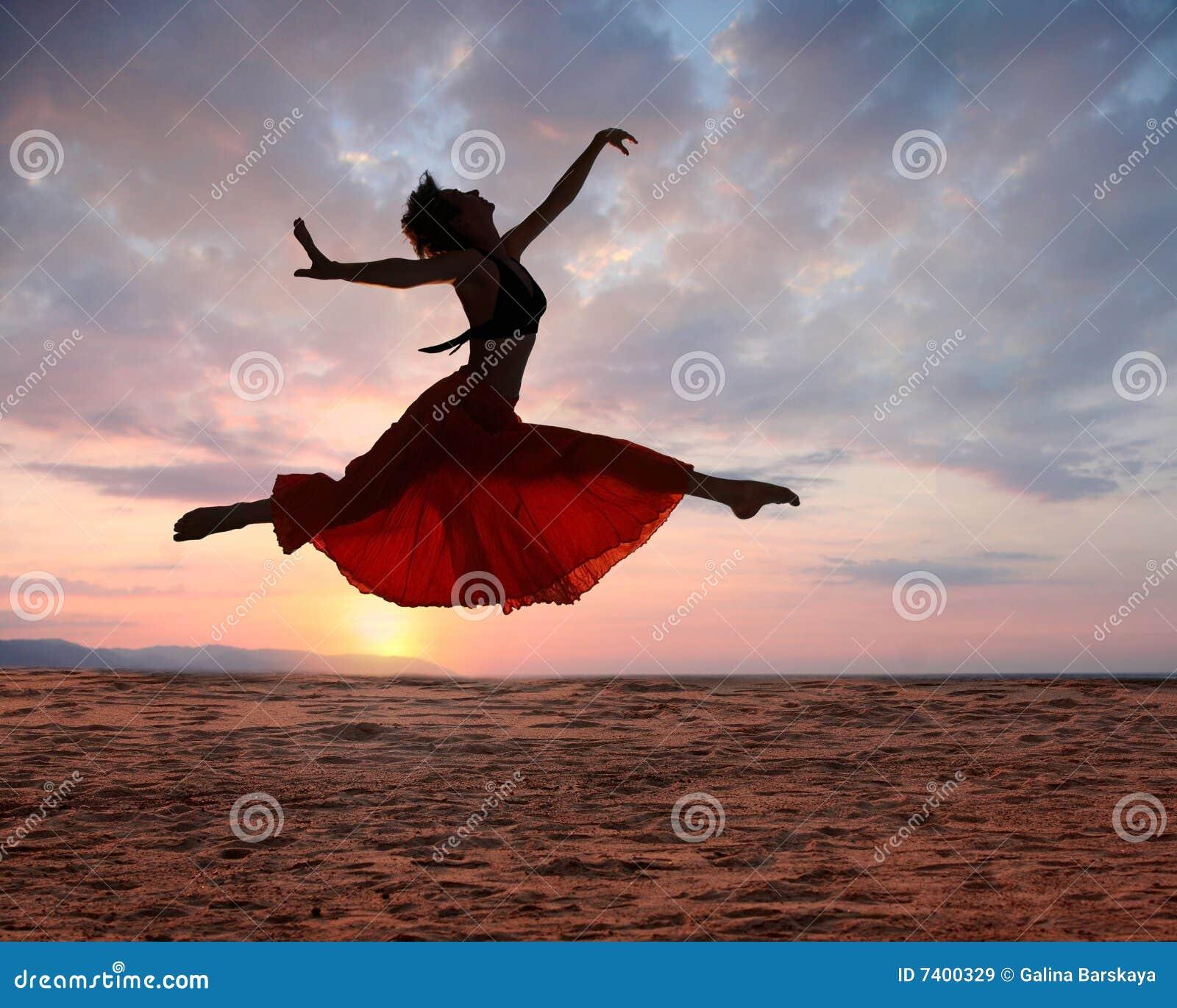 Mujer de salto en la puesta del sol