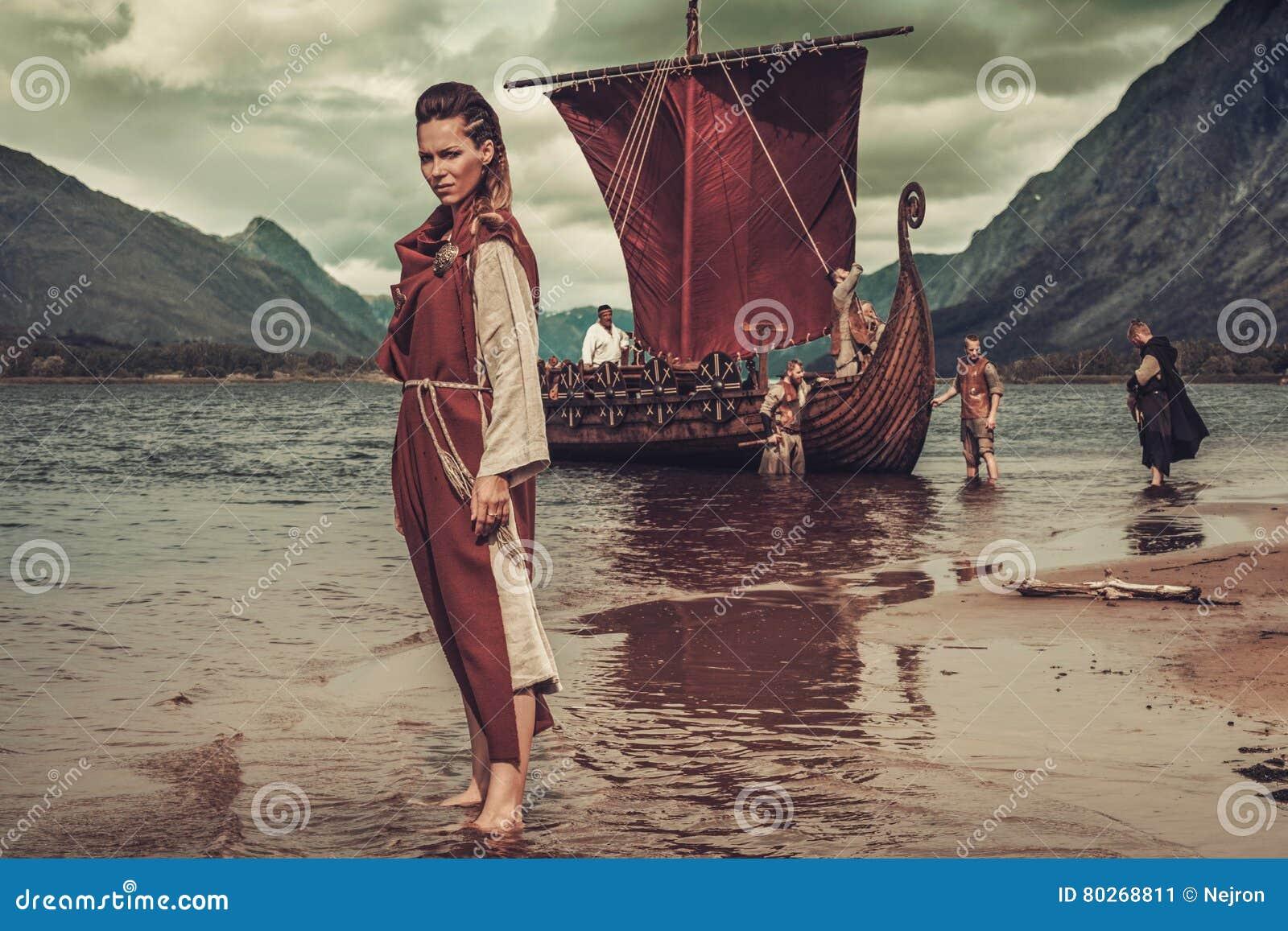 Mujer de Viking que se coloca cerca de Drakkar en la costa