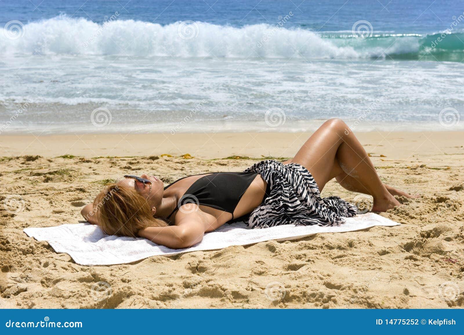 Mujer del afroamericano que toma el sol