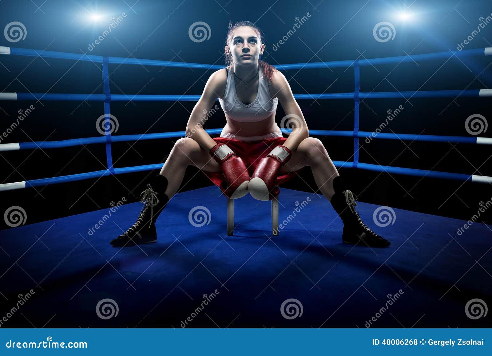 Mujer del boxeo que se sienta solamente en la arena de boxeo, rodeada por las luces azules