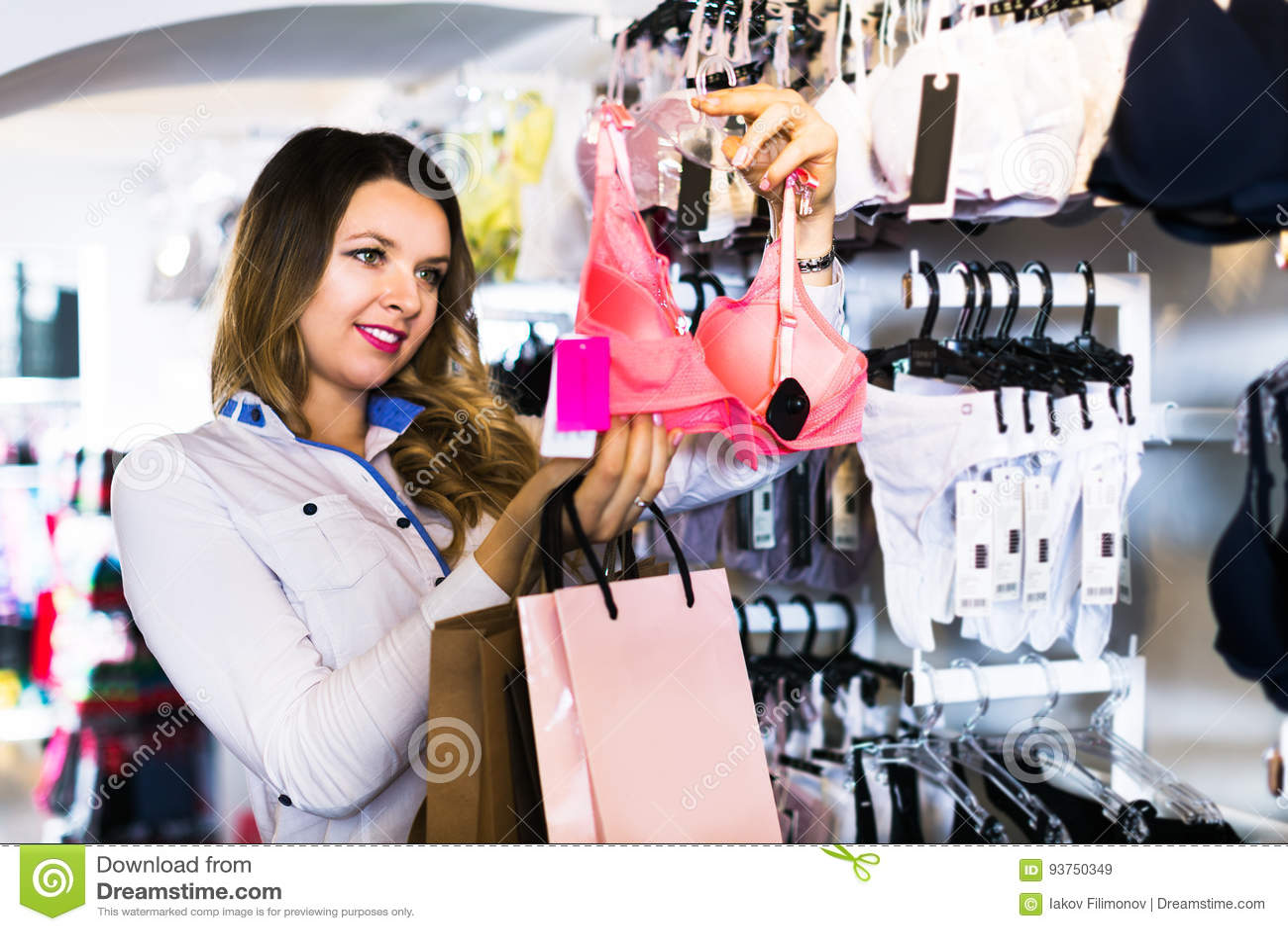a9b7d2505c Cliente femenino joven que elige el sujetador bonito en tienda de la ropa  interior