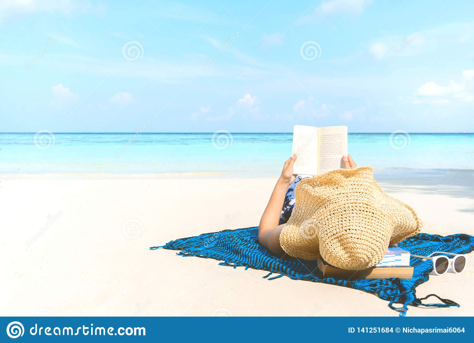 Mujer del día de fiesta de la playa del verano que lee un libro en la playa en tiempo libre