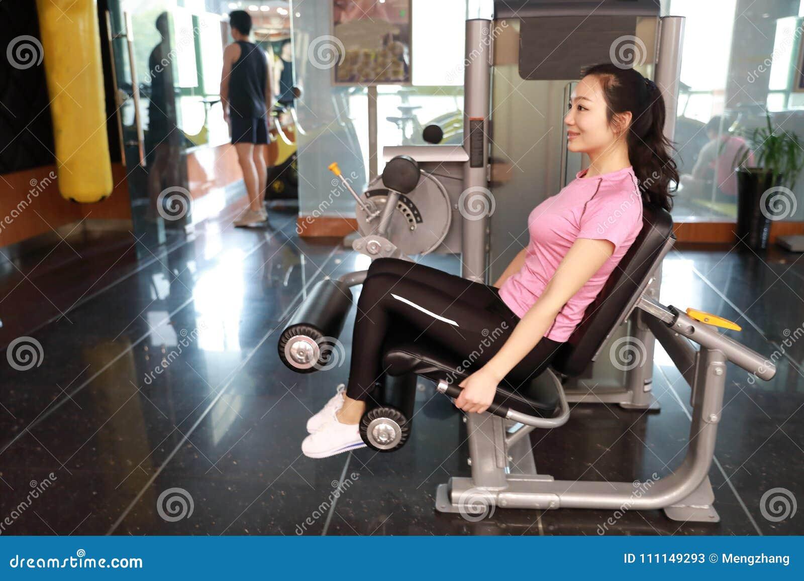 Mujer del entrenamiento del ejercicio de la extensión de la pierna del gimnasio interior Hermoso, prensa