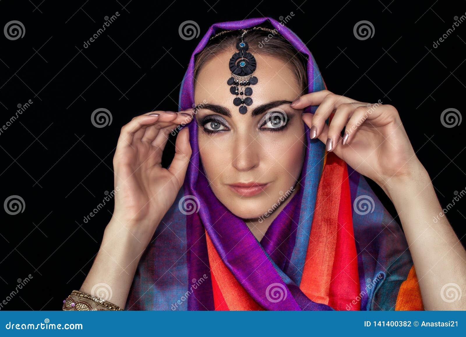 Mujer del este en burqa con las joyas en un fondo negro